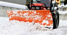 Tractor plowing snow off roads.