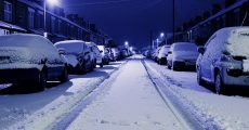 Snow covered road in city.