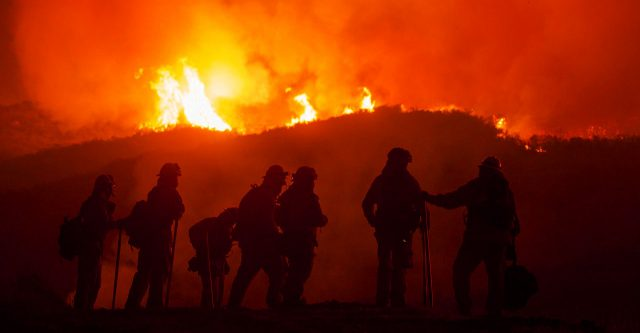 Firefighters silhouetted against flames.