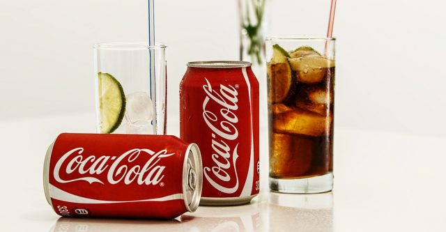Coca-Cola cans with glass cups.