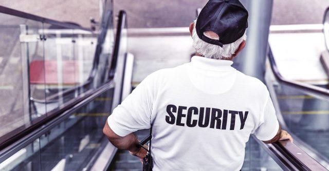 Security guy going down an escalator.