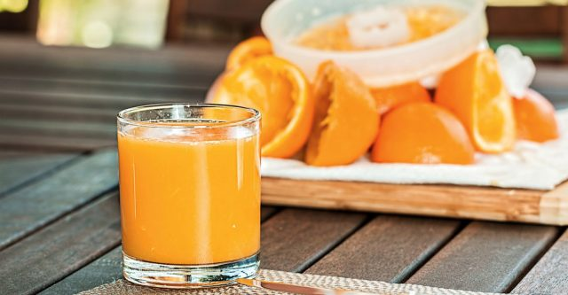 A fresh cup of orange juice on a table.