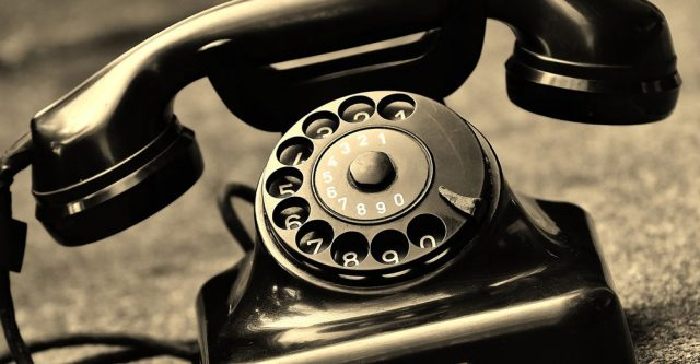 Old telephone on surface.