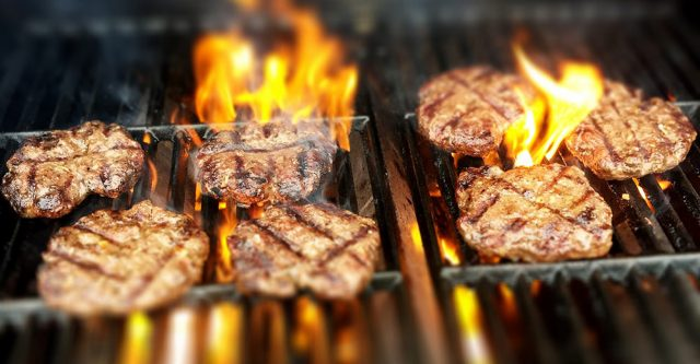 Burgers on a flaming grill.