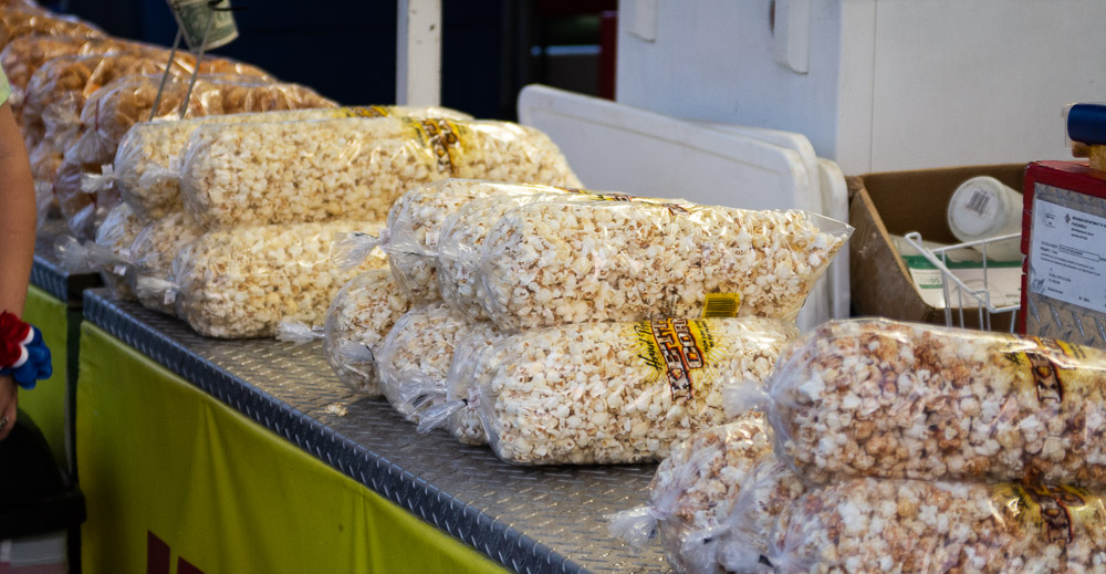 Popcorn, caramel corn, and kettle corn in bags on counter.