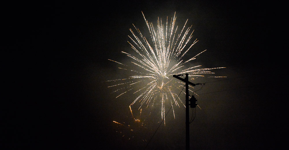Fireworks behind the electric pole.