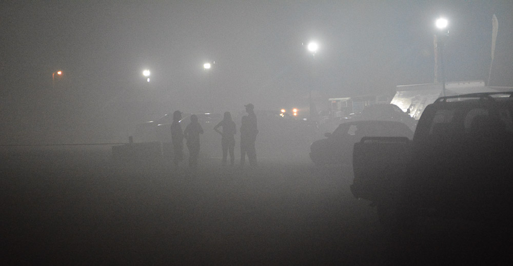 People and cars enveloped with dense smoke after fireworks show.