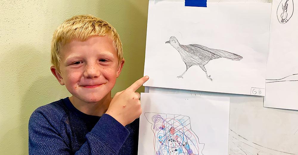 3rd grader Gideon Biring shows off his artwork