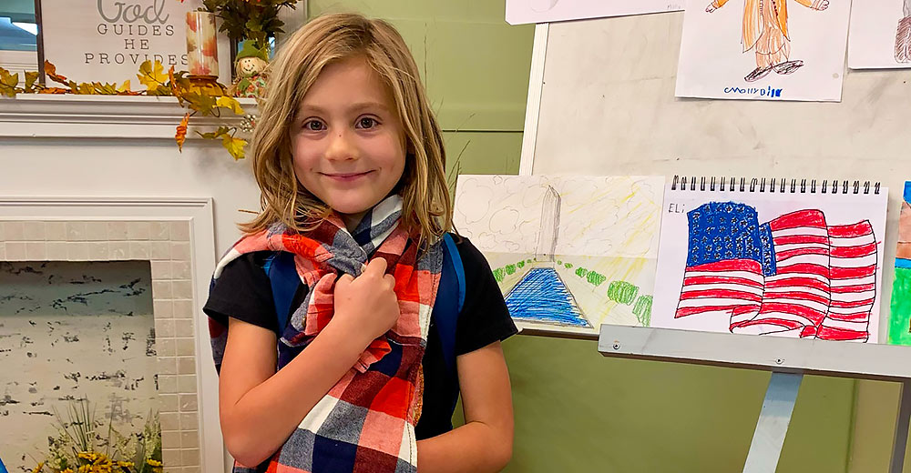 2nd grader Lillian Maxwell stands among the student masterpieces