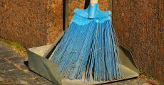 A blue broom and metal dust pan.