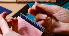 Person sewing leather together.