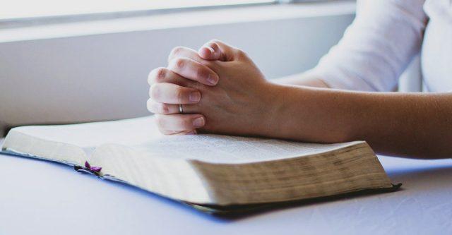 hands praying over an open Bible