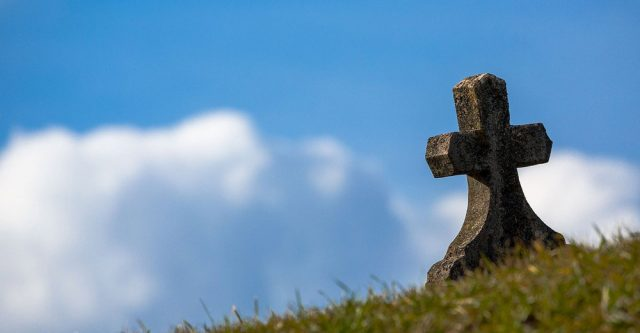 A graves tombstone on a hillside.