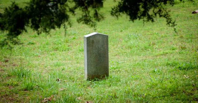Tombstone inside of a grassy graveyard
