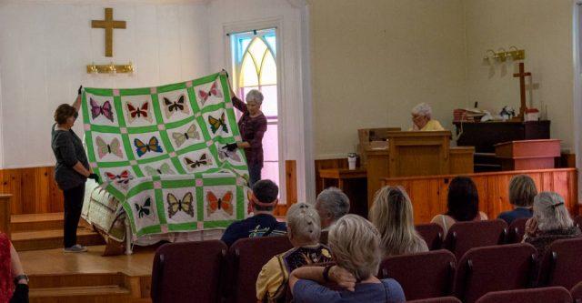"Crowd admires quilt at the 2021 Ozark ""Black Gold"" Walnut Festival Quilt Show."